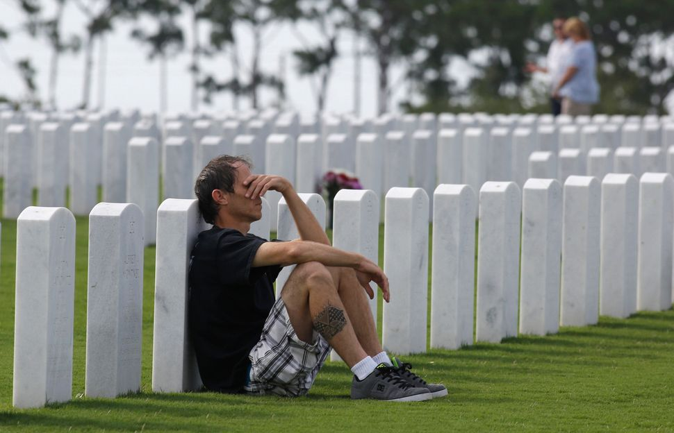 Jeff Lee of Lantana, Florida, leans against the gravestone of his father, Frank Lee, during a Memorial Day ceremony at the So