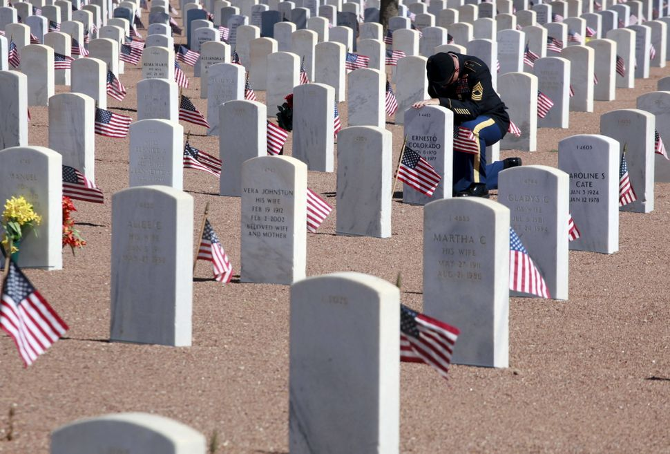 A soldier sits in front of a grave during Memorial Day celebrations at Fort Bliss in El Paso, Texas, on May 25, 2015.