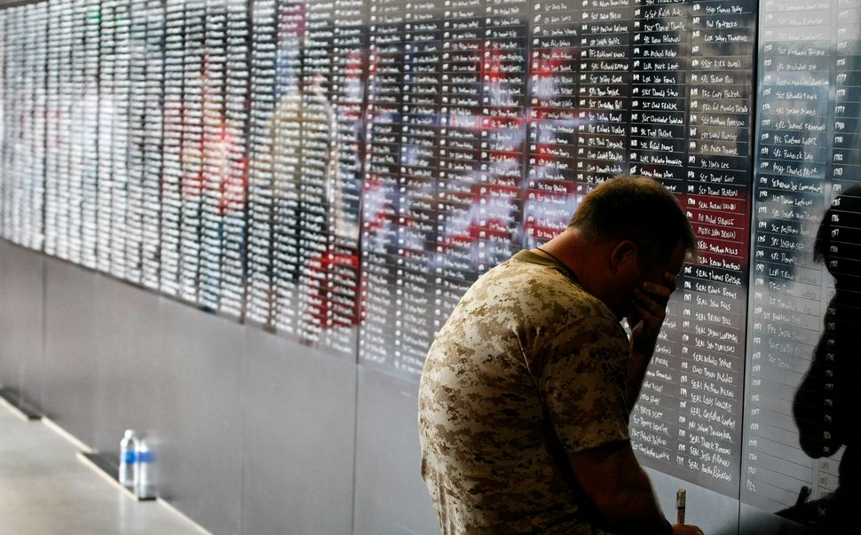Navy veteran Ron White pauses to reflect for a moment as he adds the names of over 2,000 fallen military personnel who served