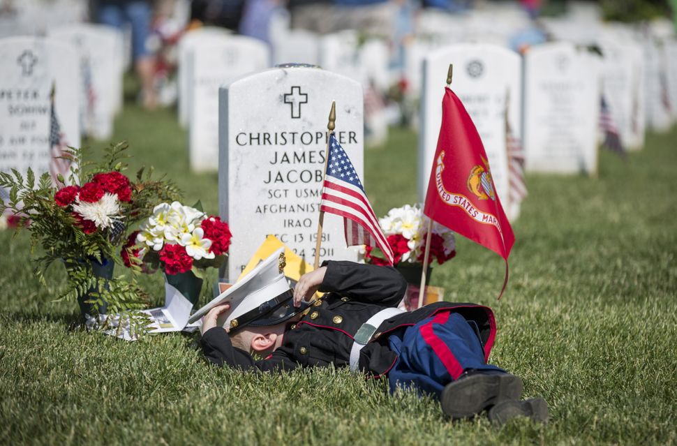 Christian Jacobs, 4, of Hertford, North Carolina, lies on the grave of his father, Christian James Jacob, during a Memorial D