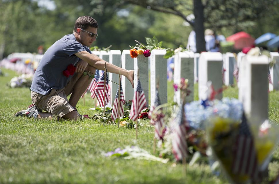 Ryan Buckingham of Camdenton, Missouri, touches the grave of his friend David Hortman during Memorial Day at Arlington Nation