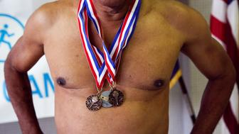 A man stands with his medals  after competing in the swimming portion of the Brooklyn Senior Games at the St. Johns Recreation Center in New York, U.S., May 11, 2016. The games celebrate Brooklyn seniors over the age of 50 competing in competitive games like bowling, basketball, swimming, board games and track and field.    REUTERS/Shannon Stapleton