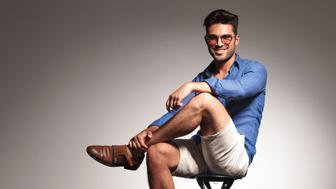 Full body picture of a casual young fashion man sitting with his legs crossed, smiling at the camera.