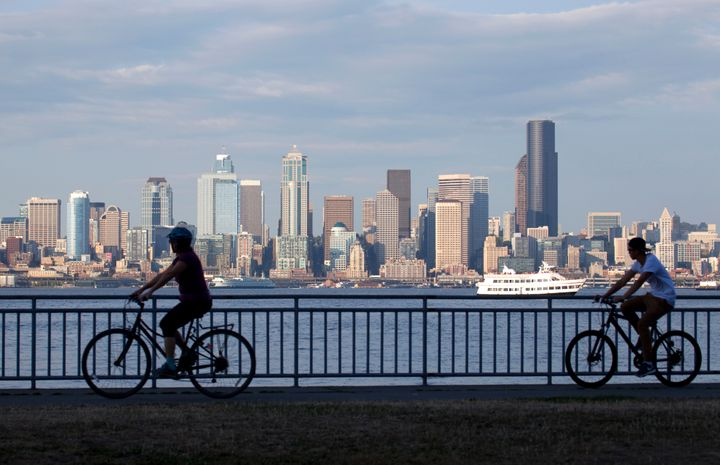 Cyclists bike near Elliot Bay, with Seattle in the background.