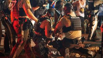 Demonstrators are arrested by police during a civil disobedience action on August 10, 2015 on West Florissant Avenue in Ferguson, Missouri. The night ended with over 10 arrests for disorderly conduct. St. Louis County declared a state of emergency Monday following a night of unrest in Ferguson, after a teenager was charged with shooting at police officers. The order was issued as an 18-year-old was charged in connection with a shootout in Ferguson August 9th  after a day of peaceful protests marking the first anniversary of the police shooting of unarmed black teenager Michael Brown.      AFP PHOTO / MICHAEL B. THOMAS        (Photo credit should read Michael B. Thomas/AFP/Getty Images)