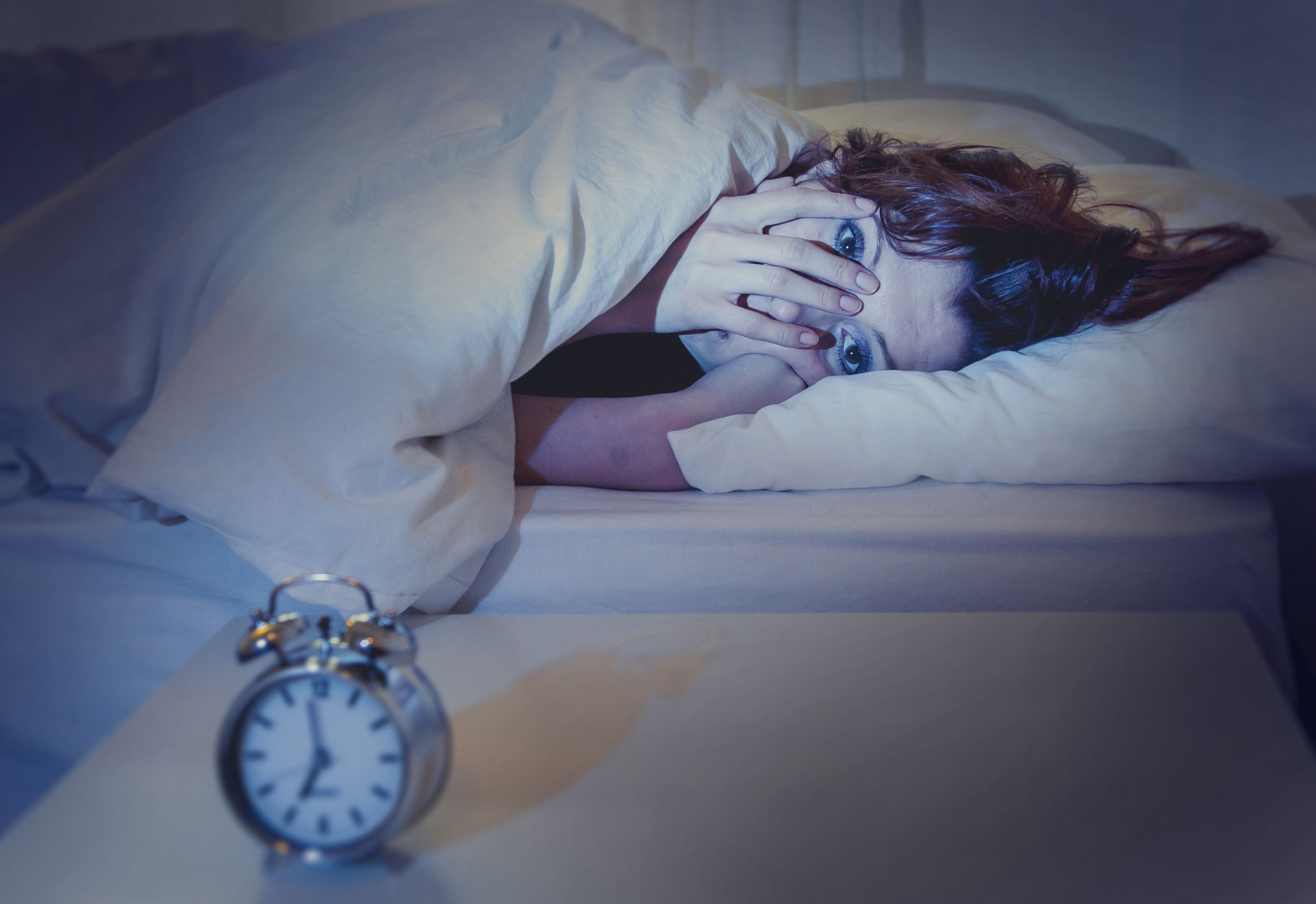 woman with red hair in her bed with insomnia and can't sleep waiting for her alarm clock to go off on a white background