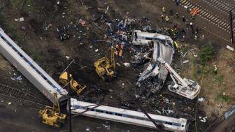 Emergency workers search for bodies inside a derailed Amtrak train in Philadelphia, Pennsylvania May 13, 2015.  Rescue workers on Wednesday sifted through twisted metal and debris from the wreck of the Amtrak train that derailed in Philadelphia, killing six people and injuring scores of others, as investigators began reviewing data to determine the cause of an accident. REUTERS/Lucas Jackson