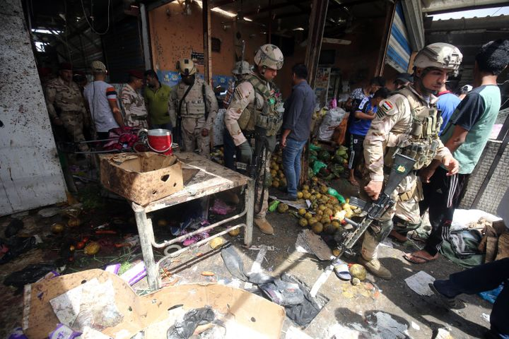 Iraqi security forces gather at the site of a suicide bombing in the Shaab area in northern Baghdad on May 17, 2016.