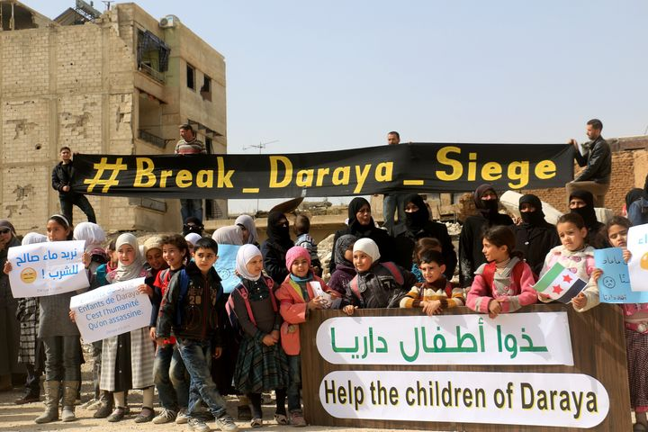 Women and children stage a protest against Assad's regime in Daraya. Government forces turned back an aid convoy that was mea