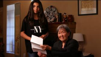 A Japanese-American woman, right, joins a Muslim-American girl in reading aloud a letter written by a child in the so-called Japanese internment camps of World War II.