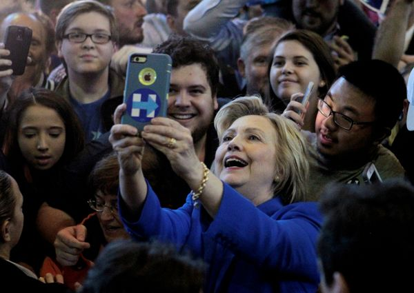 Democratic presidential hopeful Hillary Clinton takes photos with campaign supporters during a campaign rally at the Hal