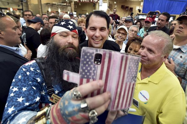 Wisconsin Gov. Scott Walker takes a selfie with supporters during a visit at a Harley-Davidson motorcycle dealership in Las V