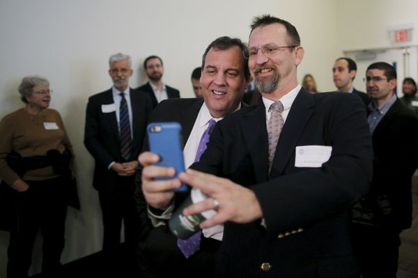 New Jersey Gov. Chris Christie (R) poses for a selfie before speaking at the New Hampshire Forum on Addiction and Heroin
