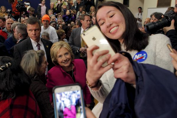 Democratic presidential hopeful Hillary Clinton poses for a selfie with audience members at a campaign town hall meeting
