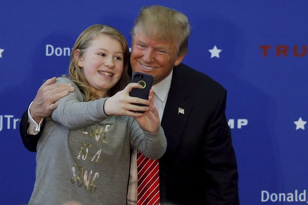 Republican presidential hopeful Donald Trump poses for a selfie with a young audience member onstage at a campaign rally in P