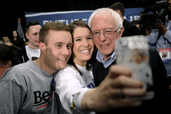 Democratic presidential hopeful Bernie Sanders poses for a selfie with supporters at a town hall in Independence, I