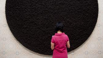 A Woman Stands In Front Of Works Of Art Called 'Black Sun' During The Press View Of Damien Hirst'S Latest Work On Display At The Tate Modern. (Photo by John Phillips/UK Press via Getty Images)