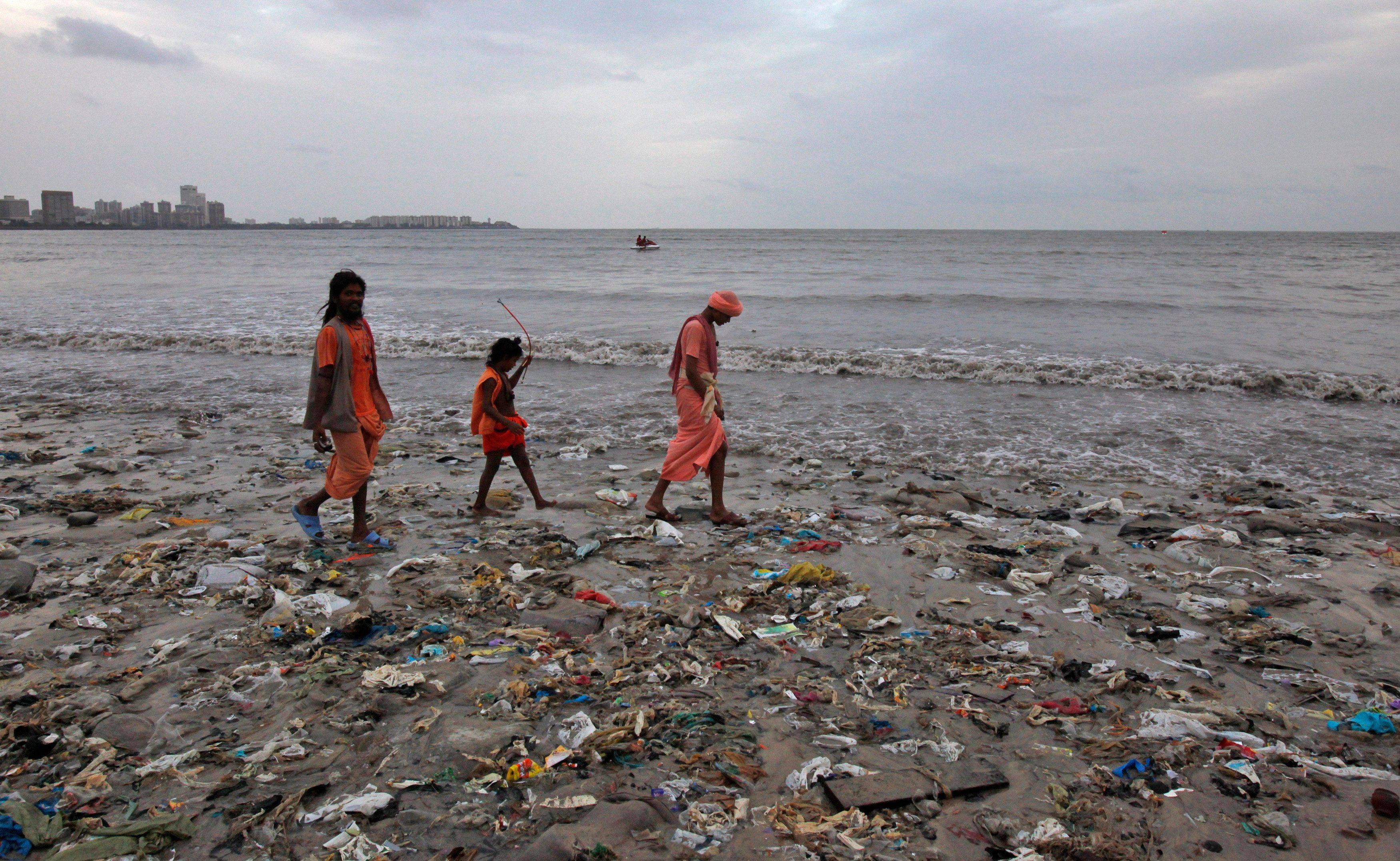 Ram Singh (L) and his relatives, dressed in traditional Hindu saffron-coloured clothes walk on a garbage-strewn beach against the backdrop of monsoon clouds on World Environment Day in Mumbai, June 5, 2012. According to the United Nations Environment Programme website, World Environment Day is celebrated annually on June 5 to raise global awareness and motivate action for environmental protection. REUTERS/Vivek Prakash (INDIA - Tags: ENVIRONMENT SOCIETY)