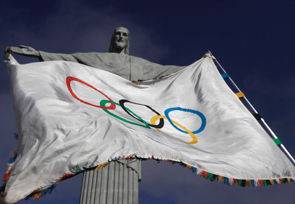 The Olympic flag flies in front of the Christ the Redeemer statue in Rio de Janeiro during a ceremony on Aug. 19, 2012.