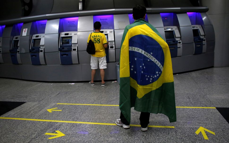 A man draped in the Brazilian flag waits inside the Banco do Brasil in Sao Paulo on March 15, 2015.