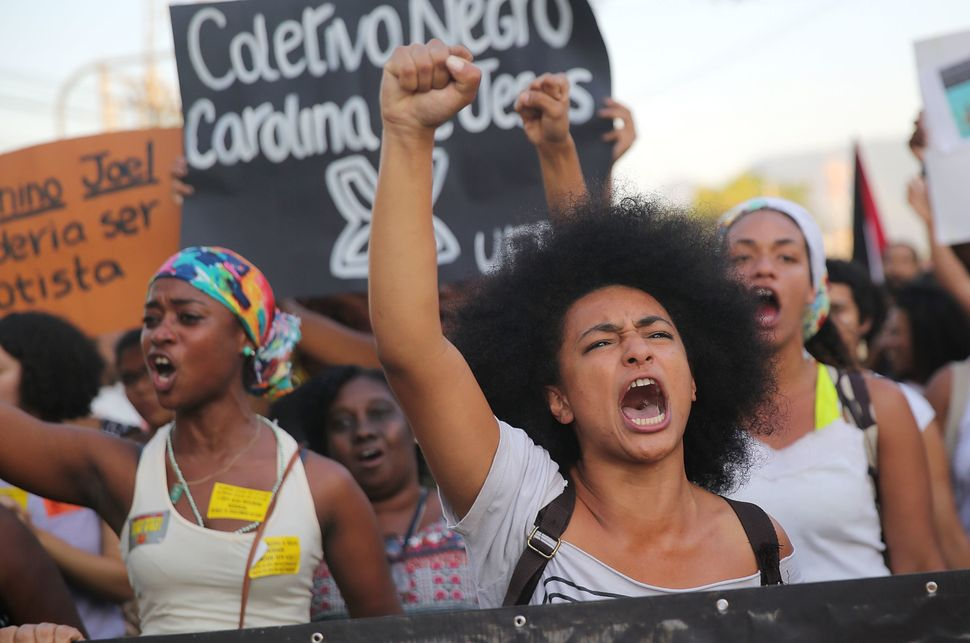 Demonstrators march through Rio de Janeiro's Manguinhos favela to protest police killings on Aug. 22, 2014.