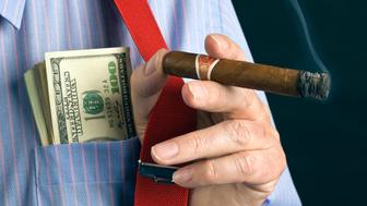 businessman with dollars, cigar and red braces.