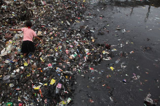An Indonesian child collects garbages on the coast near a fishing village in Jakarta,