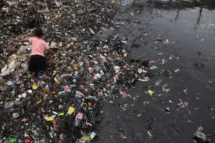 An Indonesian child collects garbages on the coast near a fishing village in Jakarta, Indonesia.