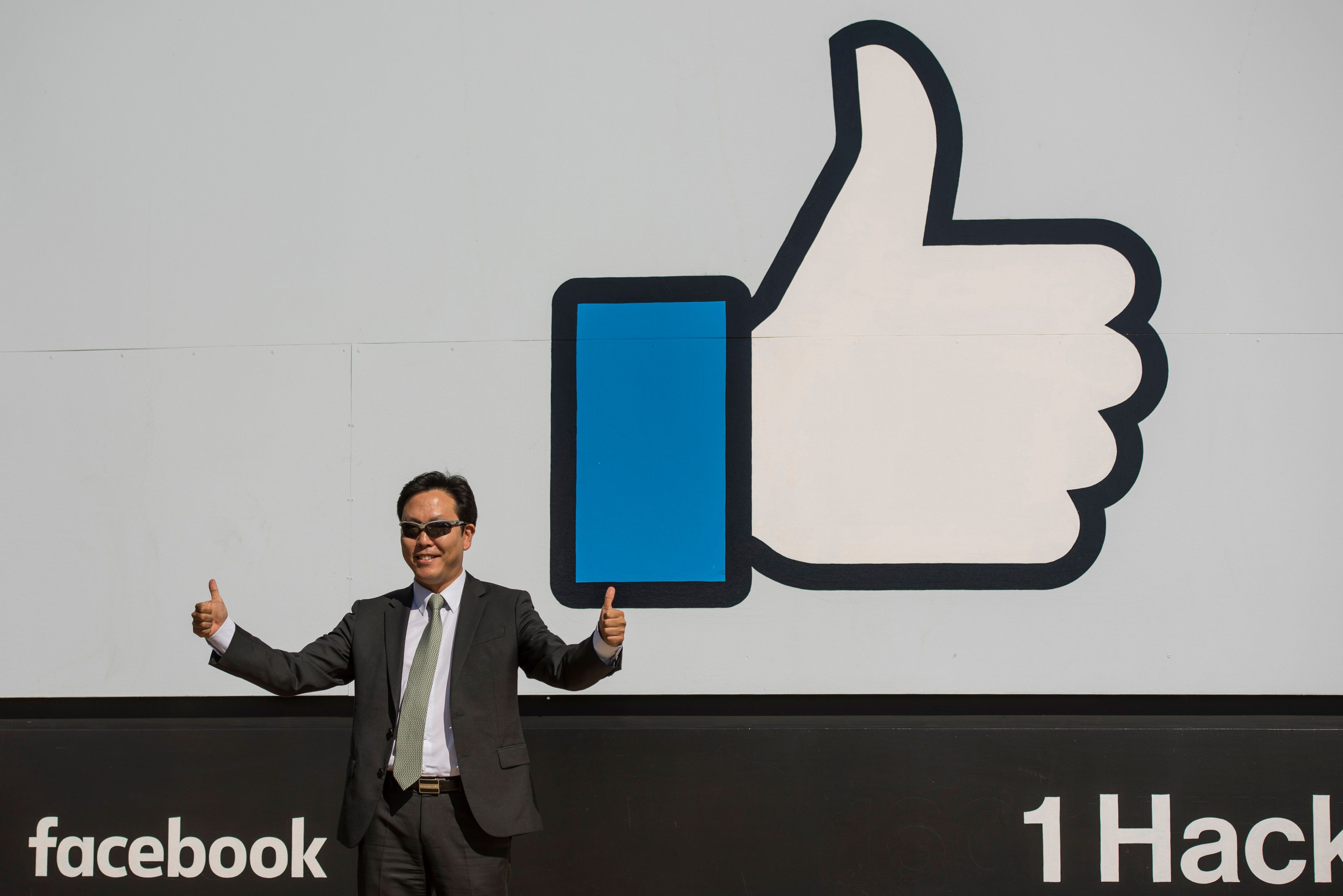 A visitor gestures while standing for a photograph in front of the 'Like' logo displayed at Facebook Inc. headquarters in Menlo Park, California, U.S., on Thursday, Oct. 22, 2015. Facebook is expected to release earnings figures on November 4. Photographer: David Paul Morris/Bloomberg via Getty Images