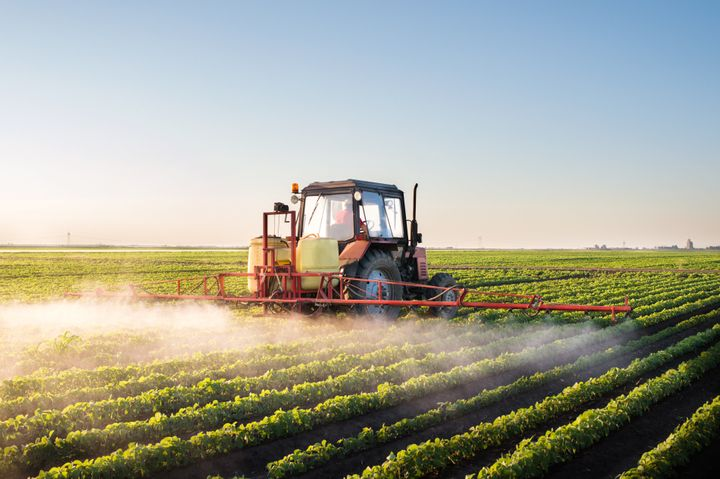 A tractor applies pesticides to a soybean field.