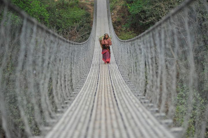 An old woman walks back home over a long bridge after collecting grass for domestic animals at Chhampi, Kathmandu, Nepal.
