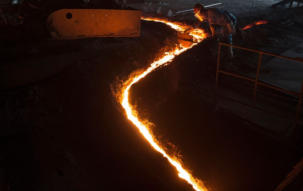 A worker moves molten iron at a furnace.