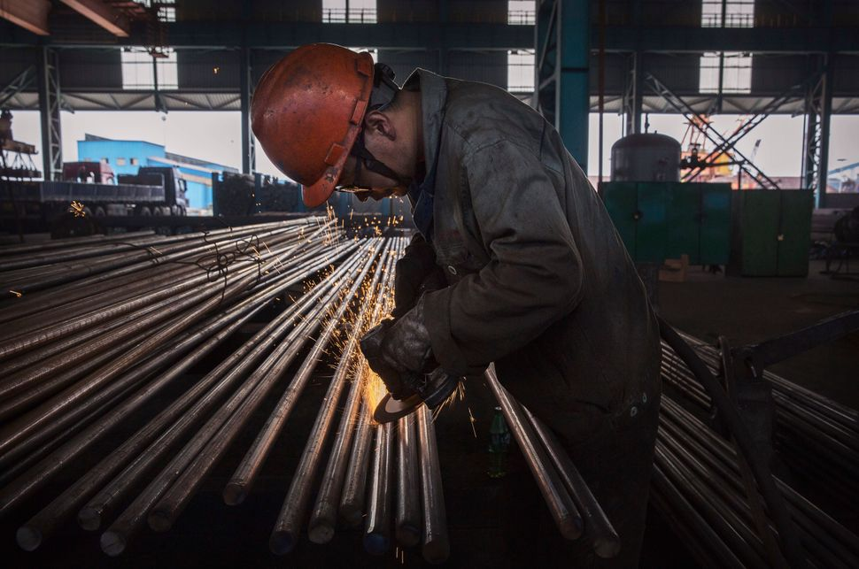 A worker welds steel bars in the production area.
