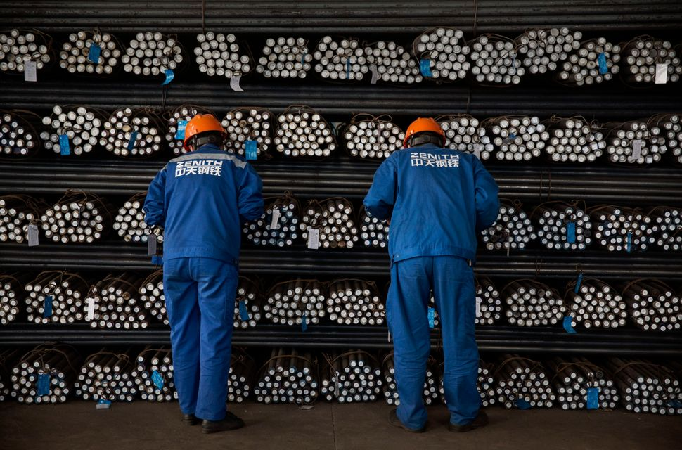 Workers inspect steel bars.