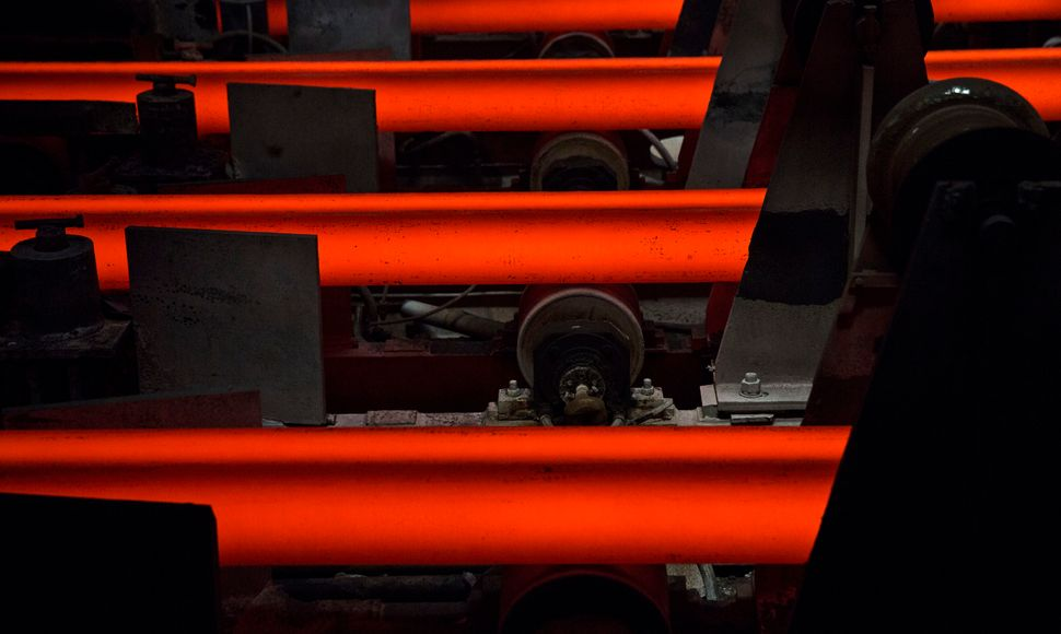A red-hot steel bar is seen on the production line.