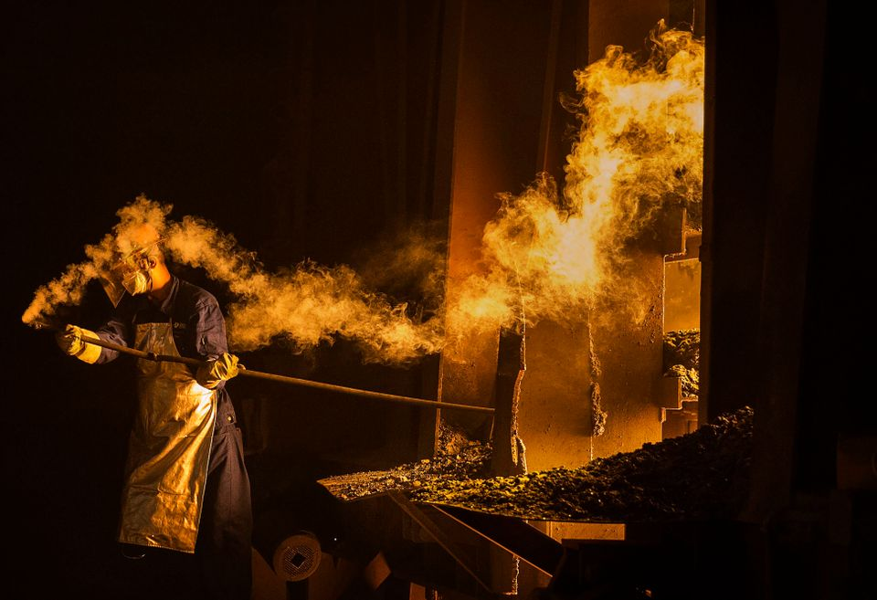 "A worker takes samples of molten iron from a furnace. ""I think the job of a steel worker is hard work almost anywhere,"""