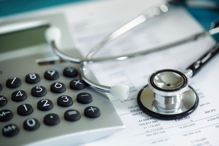 Calculator and stethoscope on financial statement concept for finance health check or cost of healthcare BrianAJackson via Getty Images