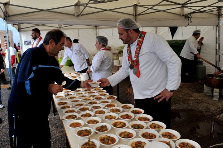 Chefs serve a free meal during an event in Greece.
