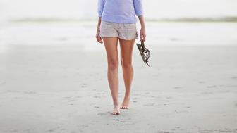 Cropped shot of the bottom half of a woman walking along the beach