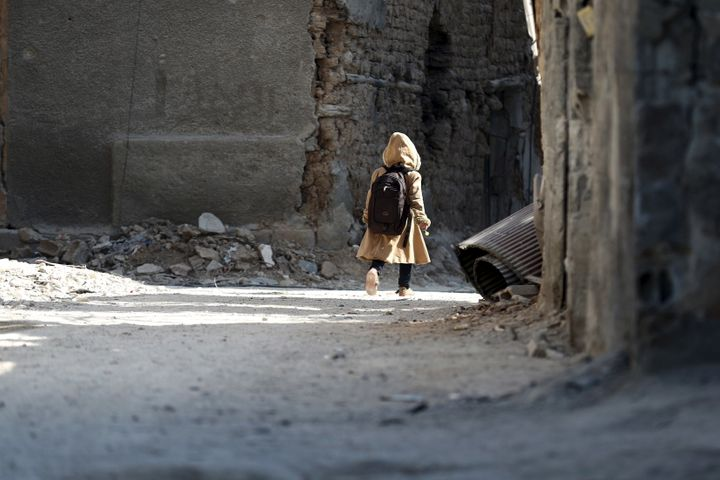 A child carries a school bag near damaged buildings in Harasta, Syria, on Jan. 30.