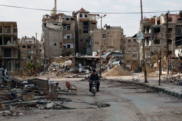 A man drives a motorbike past damaged buildings on Feb. 10 in Harasta,