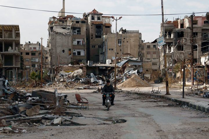 A man drives a motorbike past damaged buildings on Feb. 10 in Harasta, Syria.