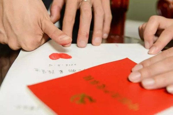 The newlyweds seal their transcription of the constitution with two red thumb prints in the shape of a heart.