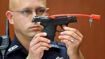 FILE PHOTO: Sanford police officer Timothy Smith holds up the gun that was used to  kill Trayvon Martin, while testifying during George Zimmerman's murder trial in Seminole circuit court in Sanford, Florida, June 28, 2013.   REUTERS/Joe Burbank/Pool/File Photo