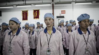 Employees line up for roll call at a Pegatron Corp. factory in Shanghai, China, on Friday, April 15, 2016. This is the realm in which the world's most profitable smartphones are made, part of Apple Inc.'s closely guarded supply chain. Photographer: Qilai Shen/Bloomberg via Getty Images