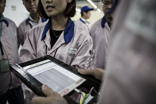 A supervisor at the Pegatron facility holds an iPad as he checks employees' names during roll call.