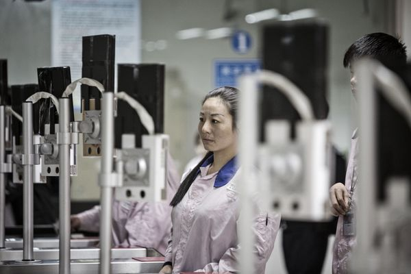 Employees look into facial recognition devices to enter the Pegatron assembly line area.