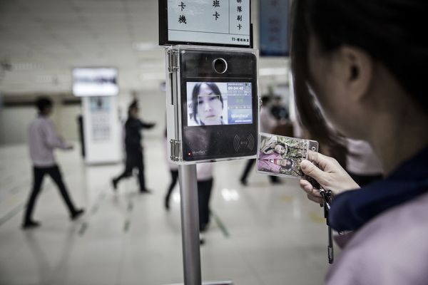 An employee uses a facial recognition device as she swipes her badge to enter the Pegatron assembly line area.