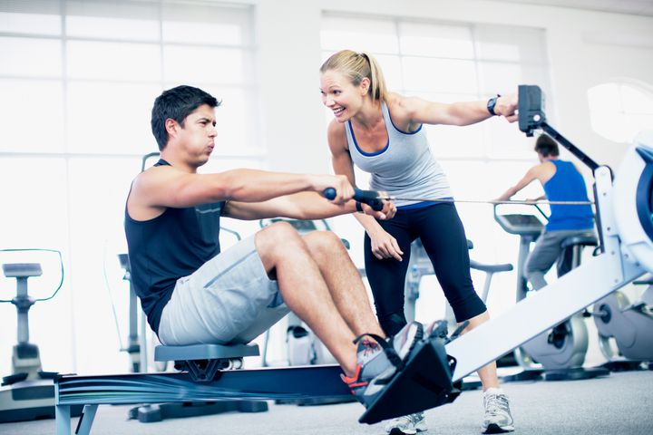 Personal trainer with man on rowing machine in gymnasium Robert Daly via Getty Images
