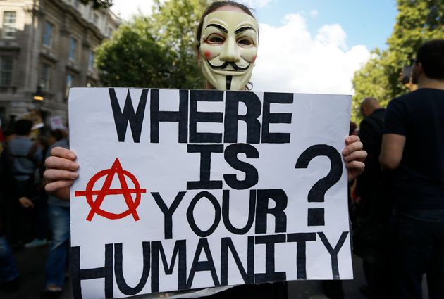 A masked demonstrator holds a banner during a Solidarity with Refugees march from Marble Arch to Parliament...